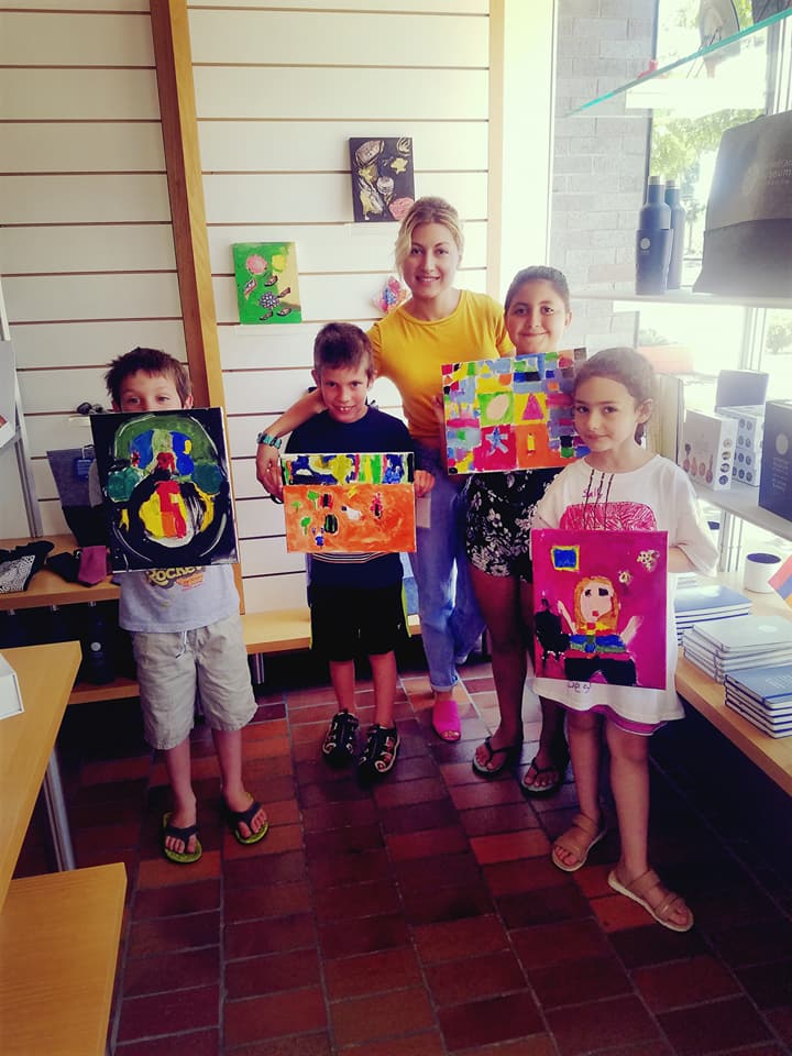 A few of the art students showing off their masterpieces with their proud teacher, Arevik, in the middle.