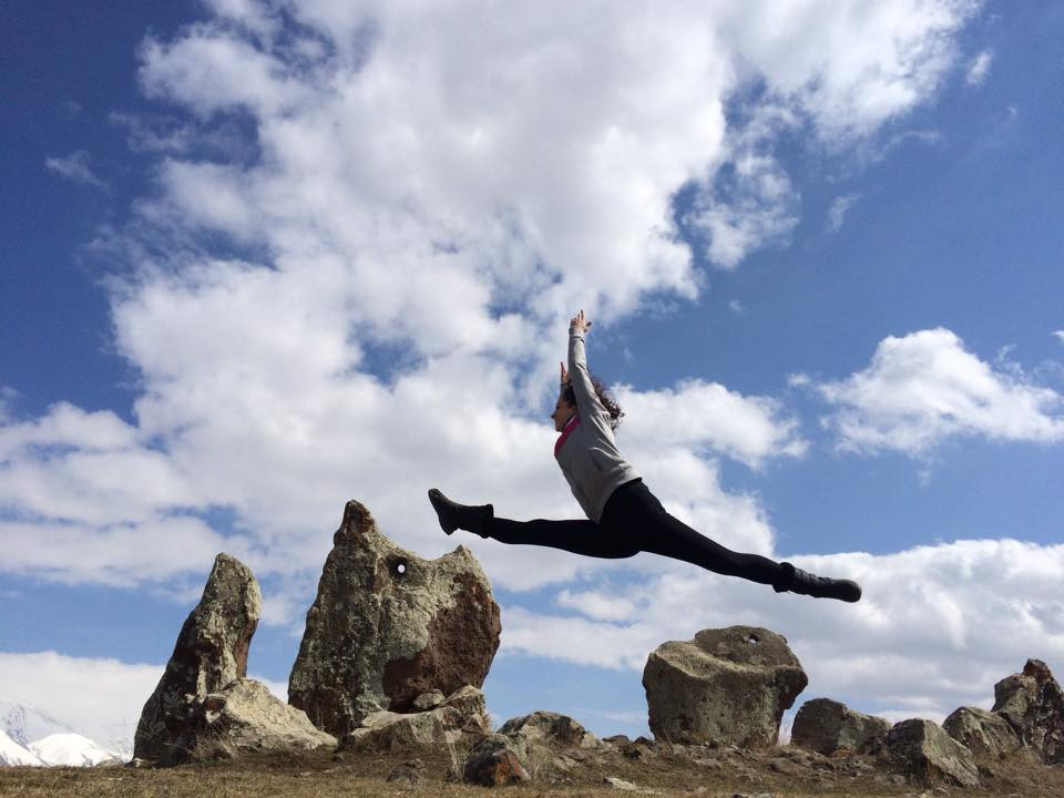 Volunteer Armina Khachatryan leaps across the monoliths at Carahunge. (Photo: Surench Photography, 2015)